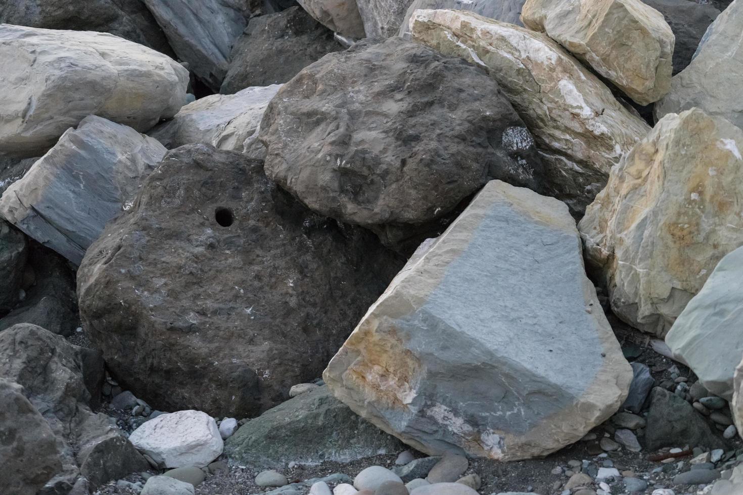 enorme stenen die op de zee liggen om de kust tegen onscherpte te beschermen foto