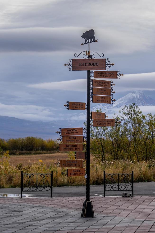een paal met een richtingaanwijzer op de achtergrond van vulkanen in kamchatka. foto