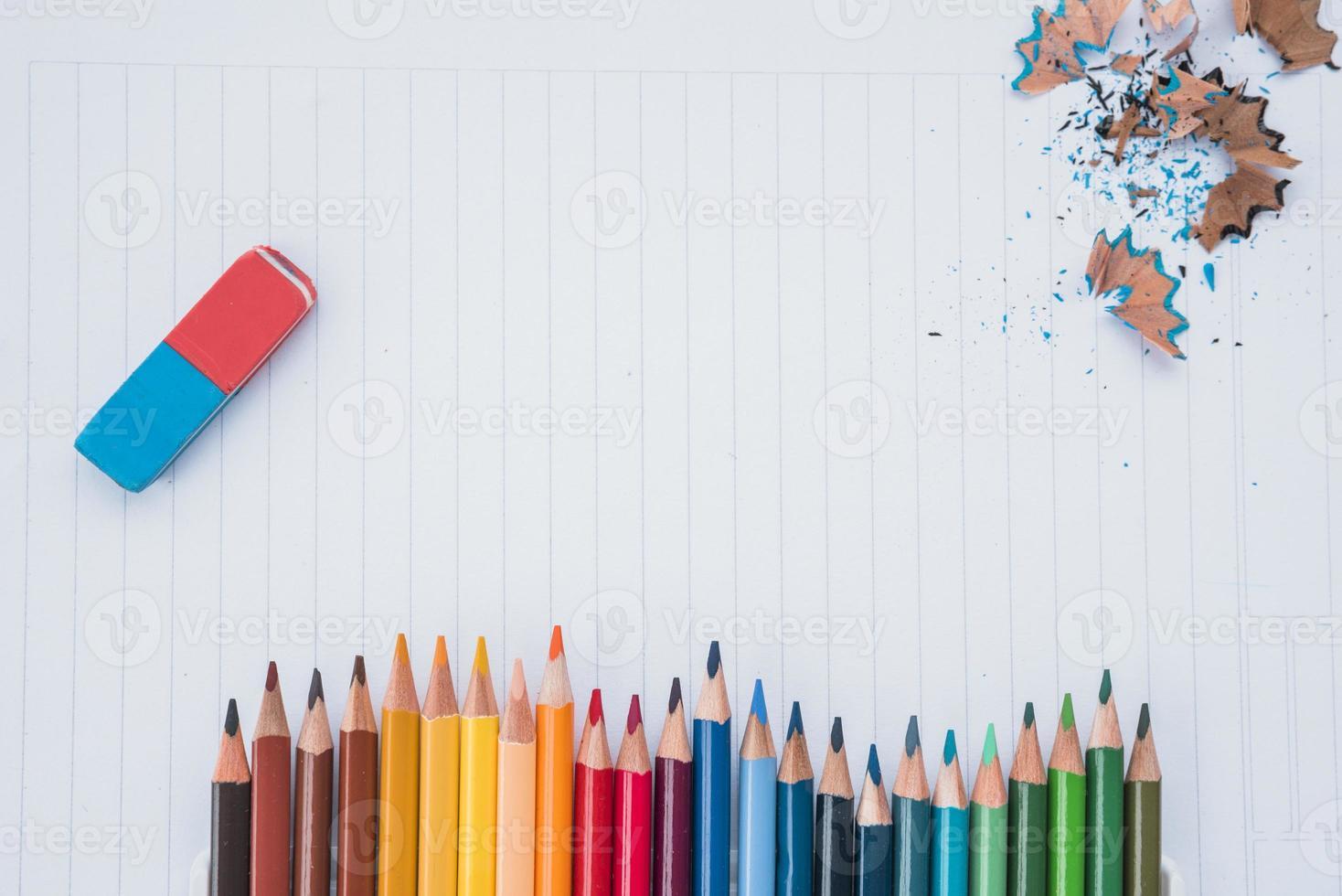 rij potloodkleuren met gum en potloodkrullen op wit papier foto