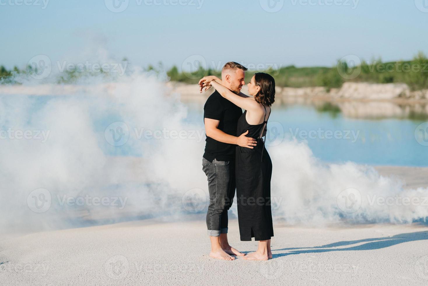 jongen en een meisje in zwarte kleding knuffelen in witte rook foto