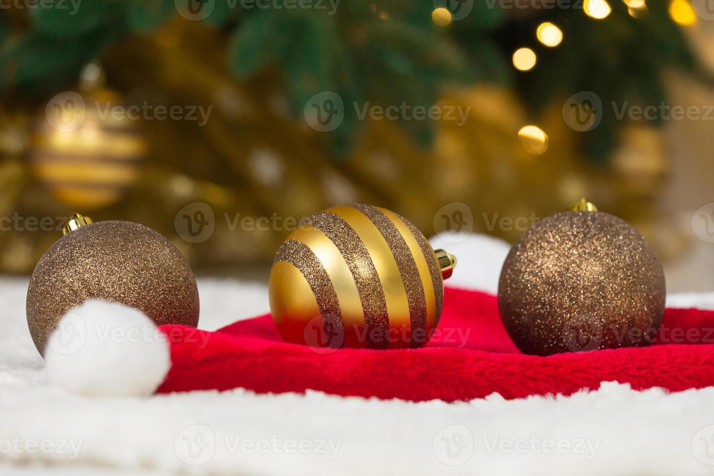 gouden kerstballen op kerstman hoed en kerstboom foto