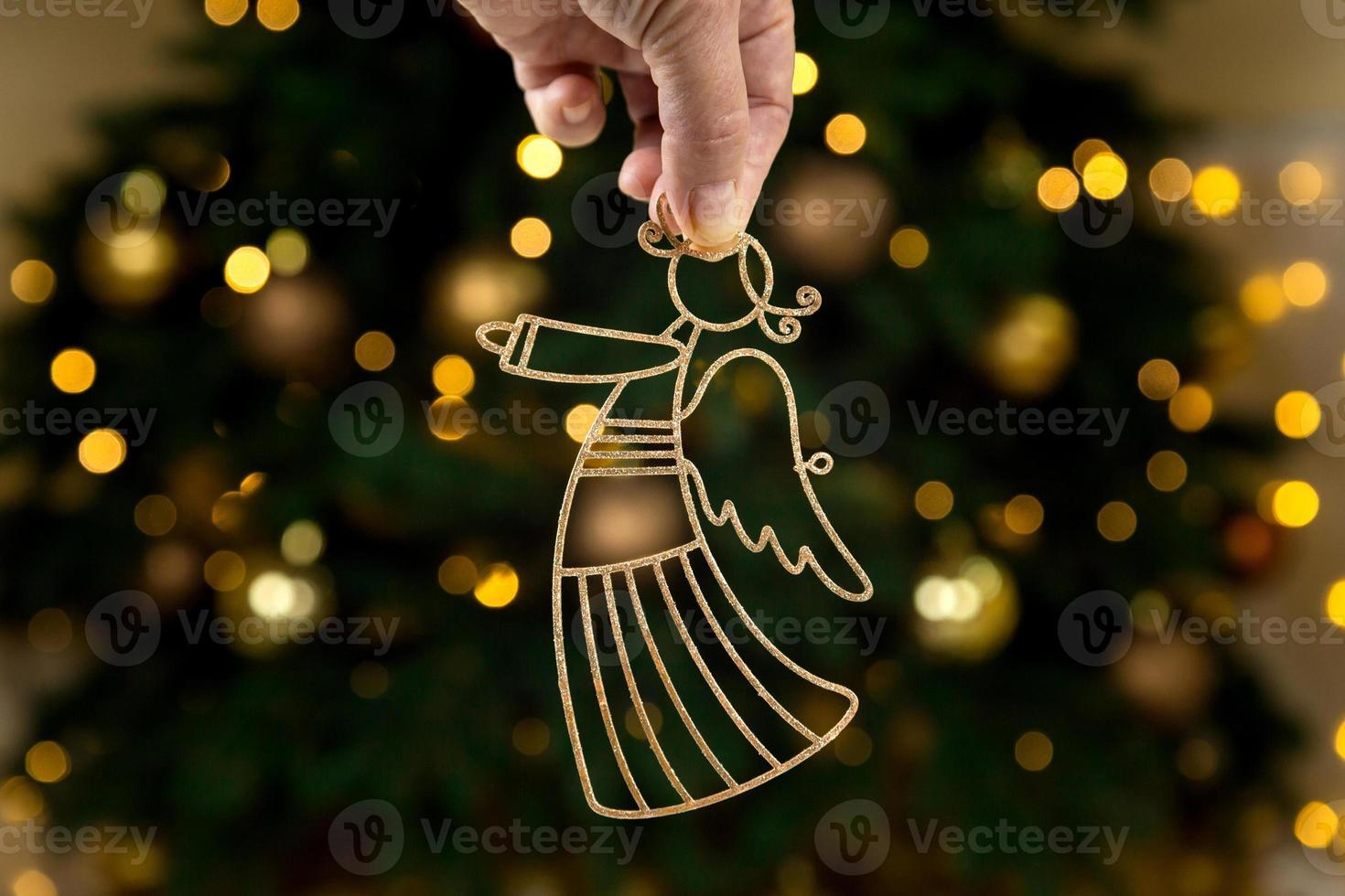 Kerst gouden engel in hand op boom achtergrond foto