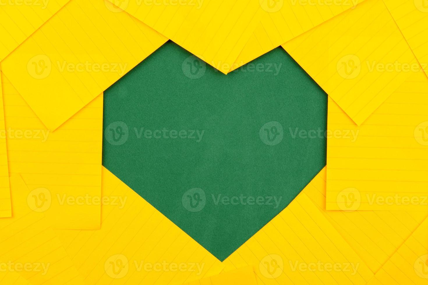 oranje vellen papier op een groen schoolbord vormen een frame hartvorm foto