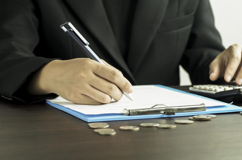 zakelijke vrouwen schrijven op nota boek met rekenmachine in de ochtend foto