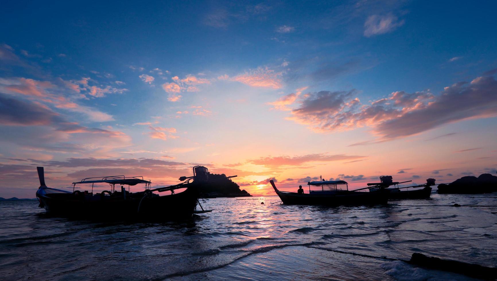 silhouet van houten boot in overzees met zonsondergang en blauwe hemel bij lepe-eiland in Thailand foto