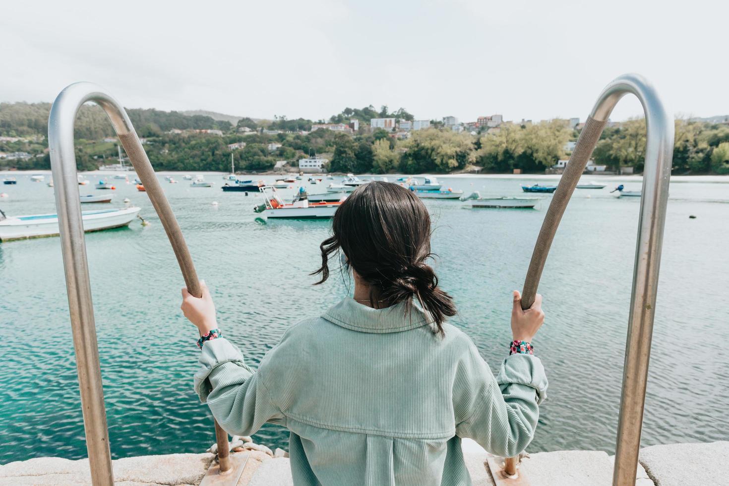 vrouw achteruit voor de zee met veel boten foto