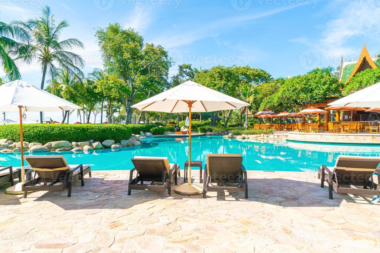 mooie parasol en stoel rond zwembad in hotel en resort foto
