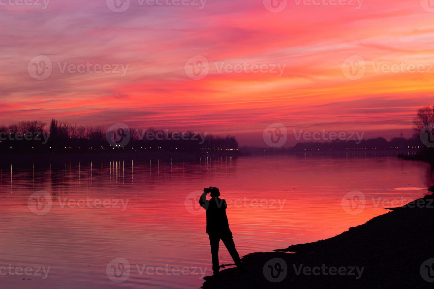 silhouet van een man die een foto maakt van een prachtige zonsonderganghemel met kopieerruimte
