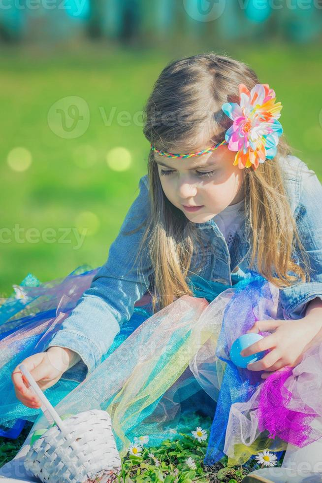 klein meisje in het park, met paasei en mand foto