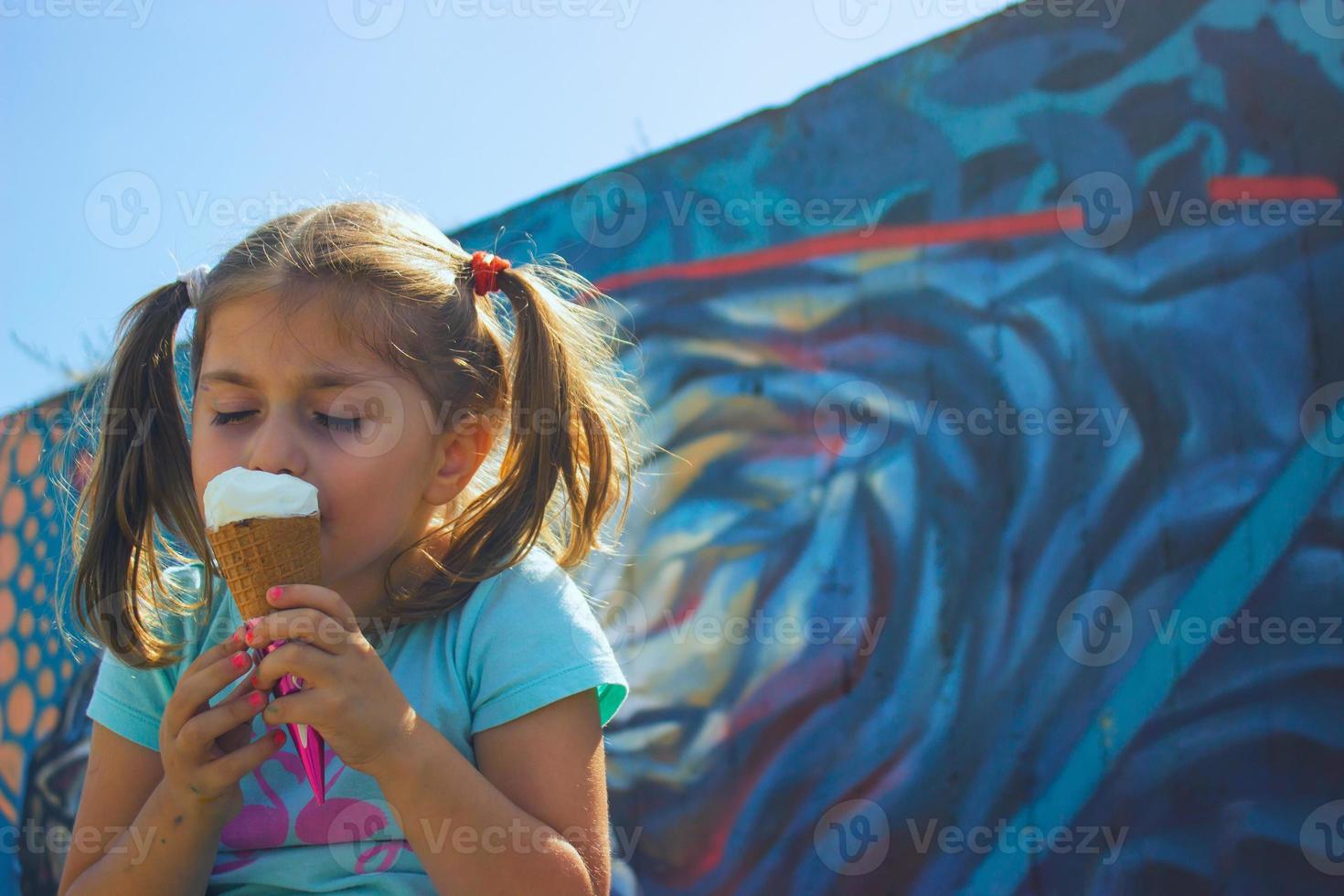 klein meisje dat ijs eet met haar ogen dicht, tegen een blauwe muur foto