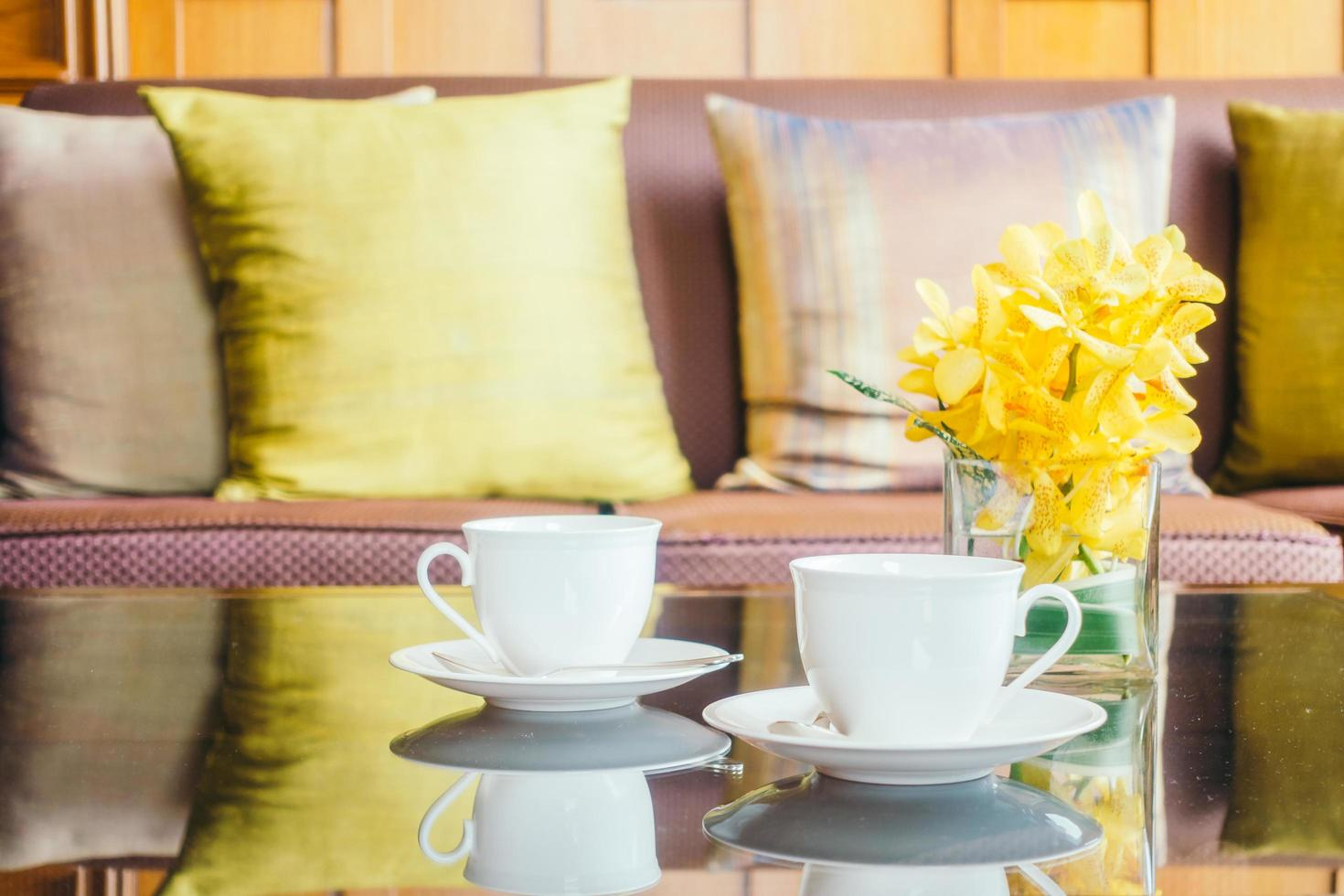 vaas bloem en witte koffiekopje op tafel en kussen op de bank foto