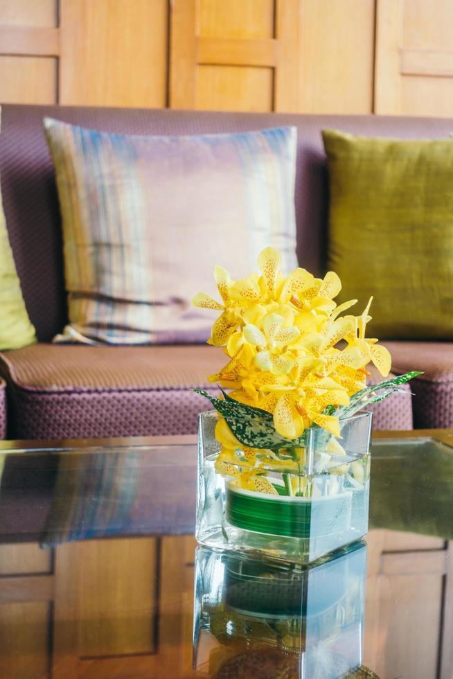 vaas bloem op tafel met kussen op bank foto