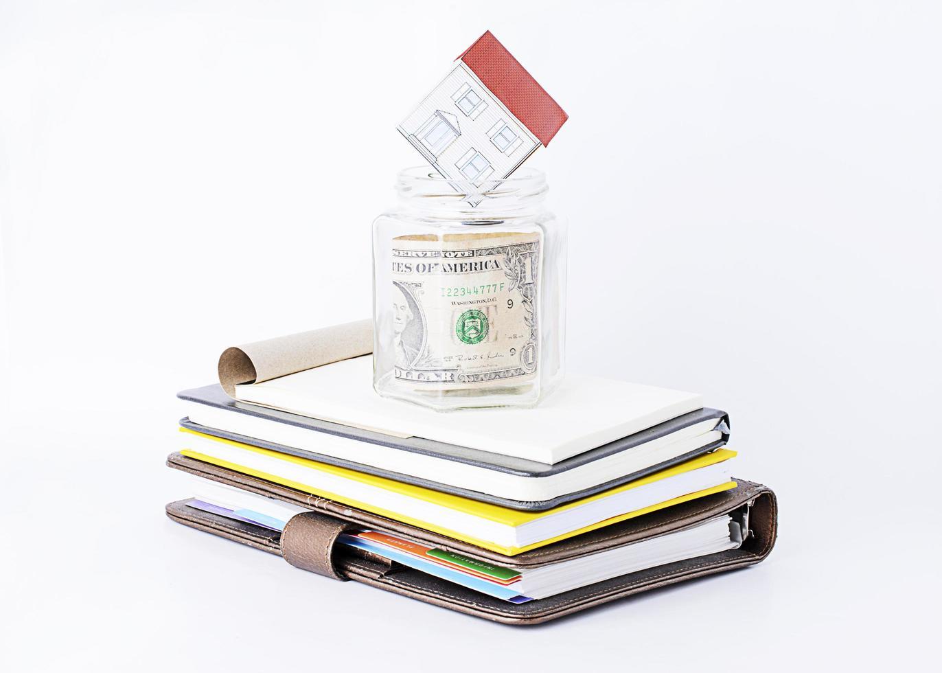 papier naar huis in glas besparen op stapel boeken foto