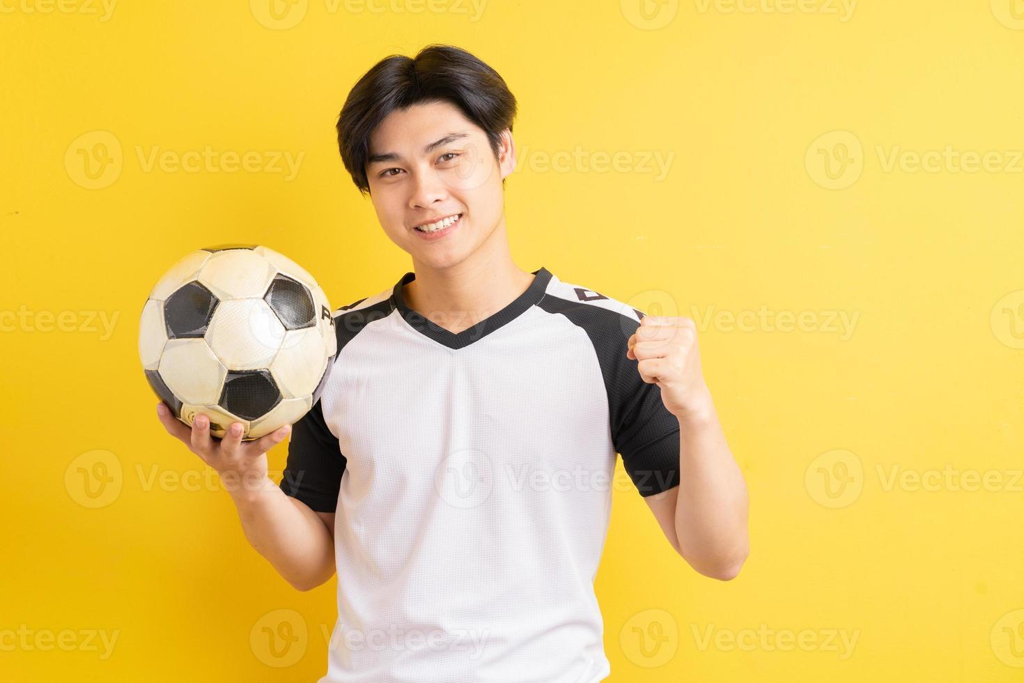 de aziatische man houdt de bal vast en toont een triomfantelijke uitdrukking foto