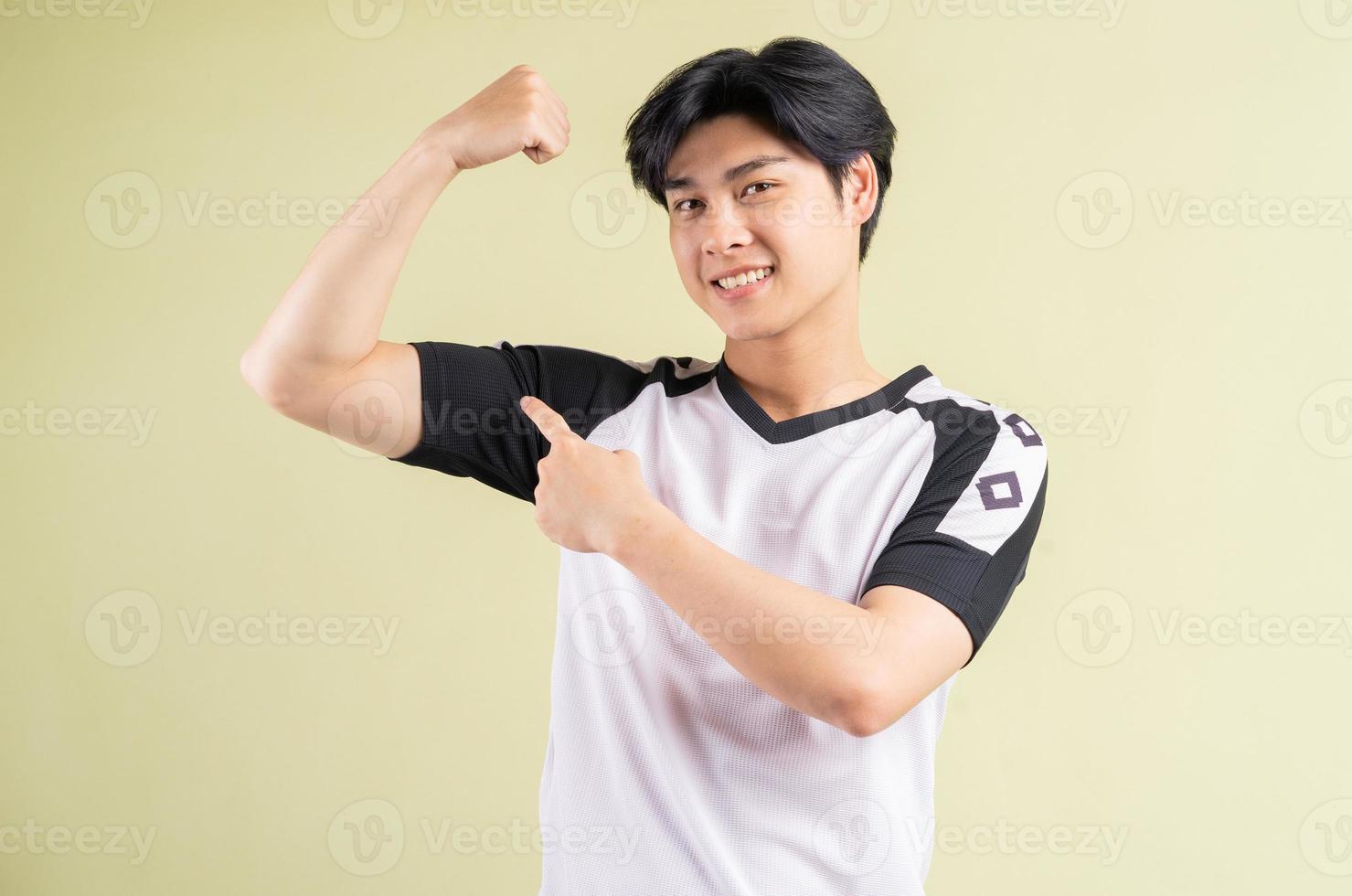de Aziatische man pronkt met zijn spieren his foto
