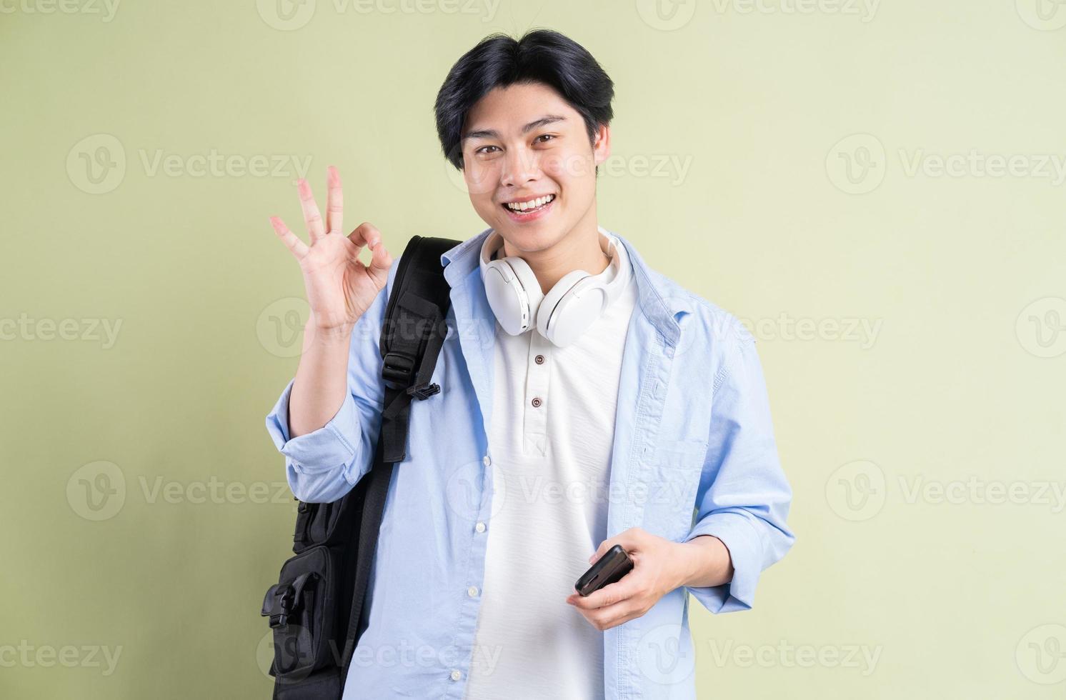 mannelijke aziatische student glimlacht en creëert een ok-symbool in de hand foto