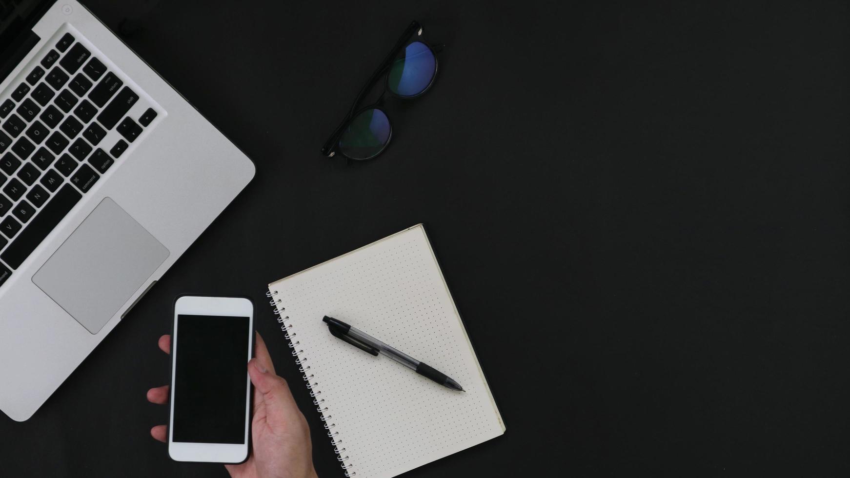 hand met smartphone laptop notebook op zwarte achtergrond foto