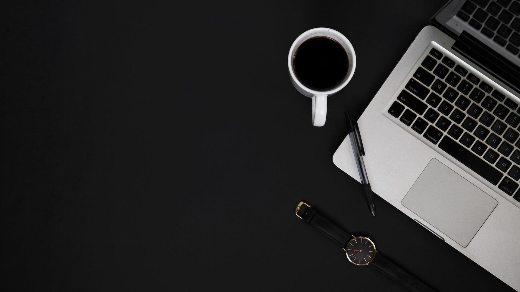 bovenaanzicht werkruimte met laptop pen horloge en koffiekopje foto