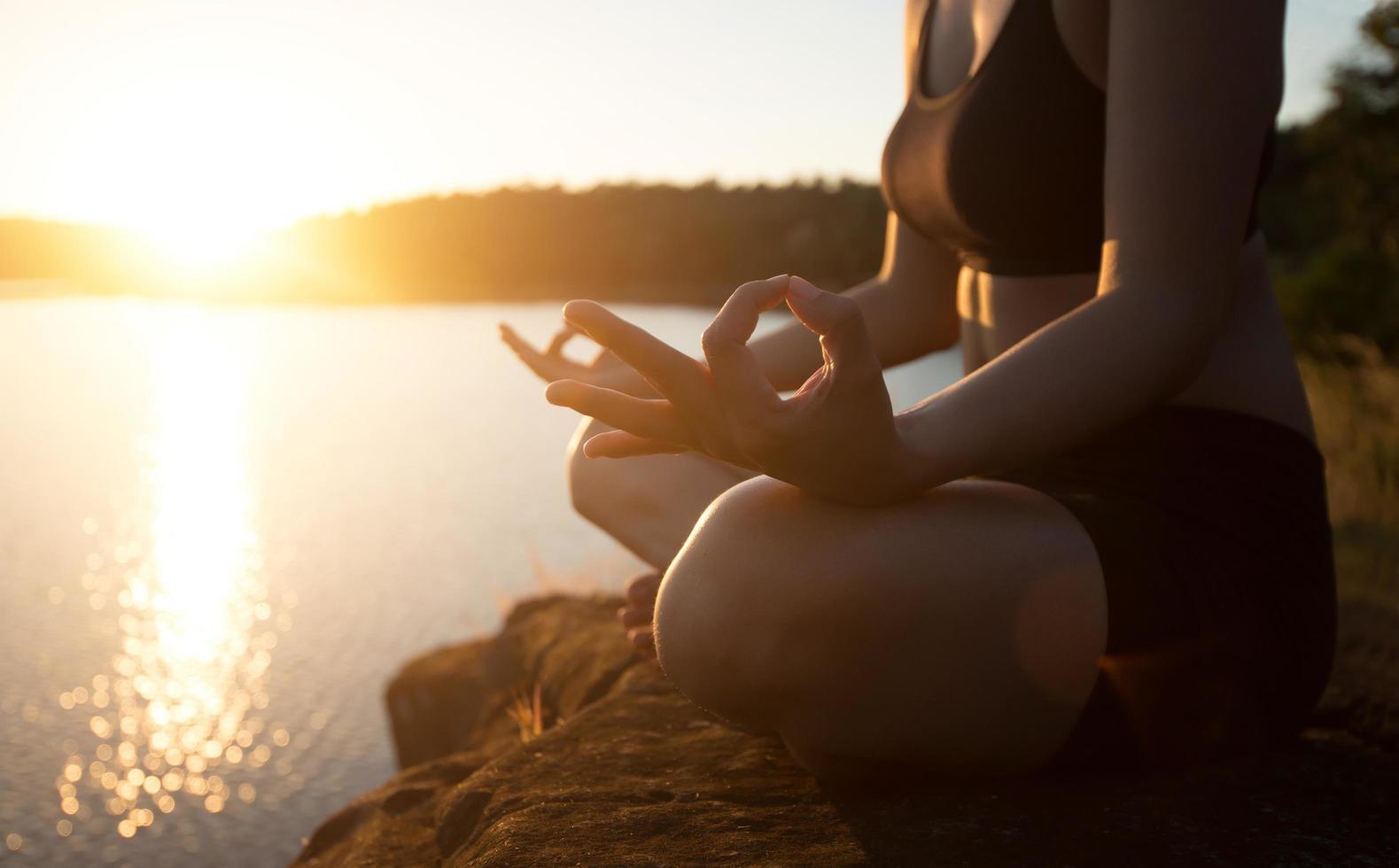 jonge gezonde vrouw beoefent yoga bij bergmeer tijdens zonsondergang. foto