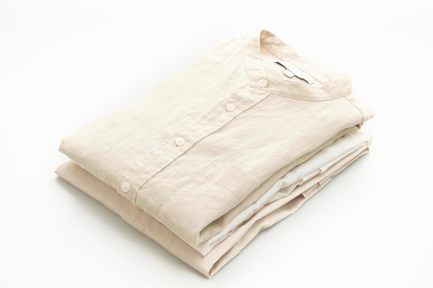 beige overhemden gevouwen geïsoleerd op een witte achtergrond foto