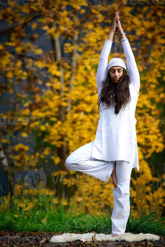 jonge vrouw tijdens een yoga practice in de herfst natuur foto