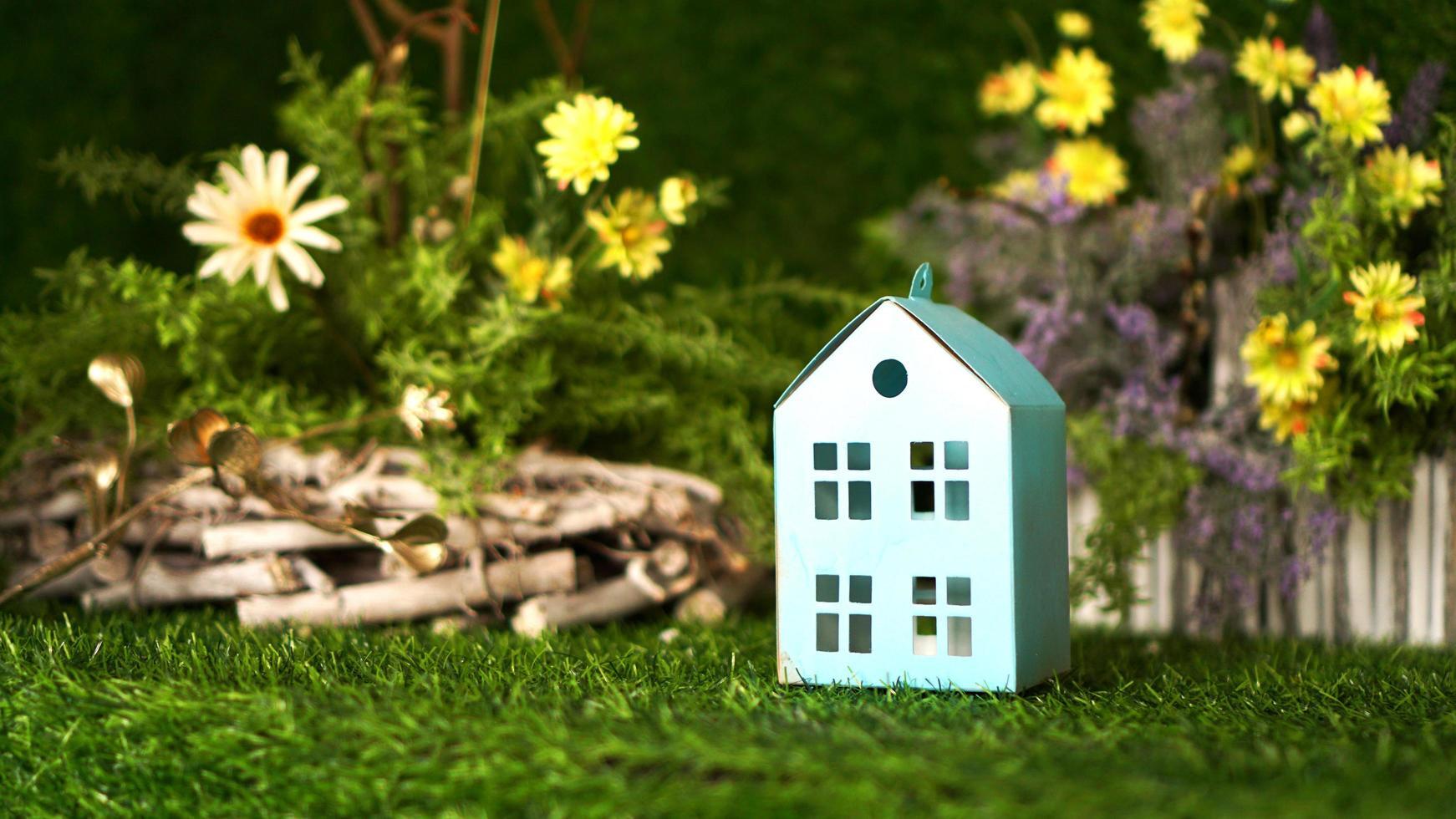 kartonnen blauw huis op de achtergrond van de groene lente foto