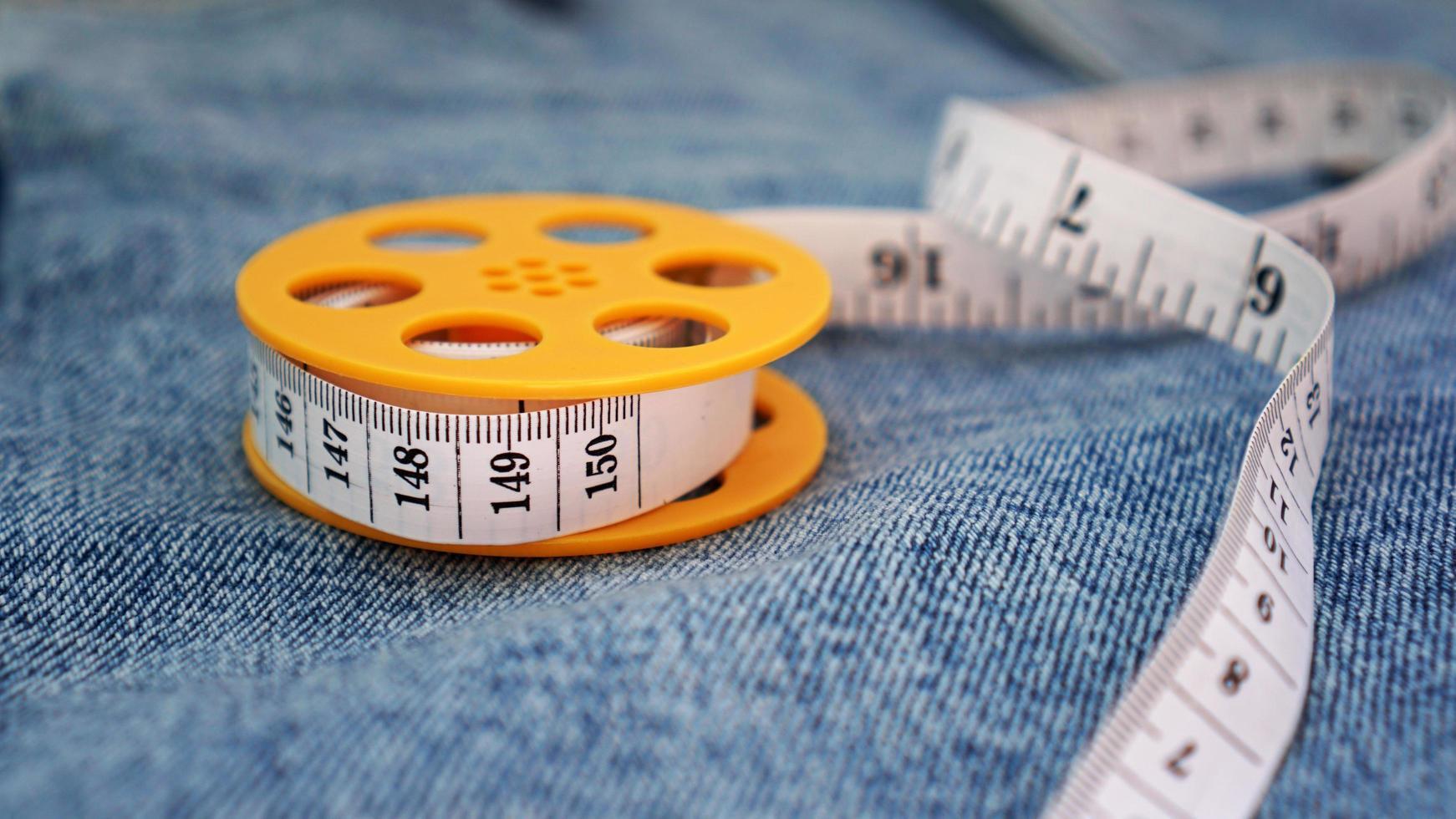 blauwe spijkerbroek en een meetlint. afslanken of naaien denim concept foto