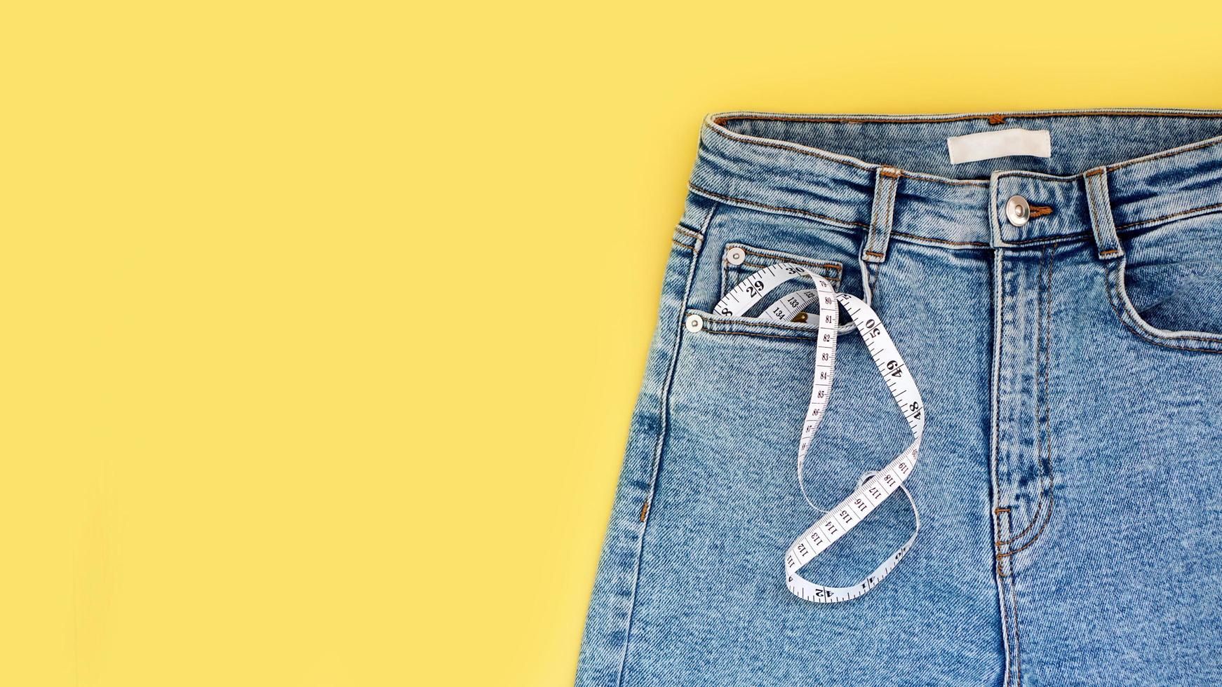 meetlint en jeans op een felgele achtergrond foto