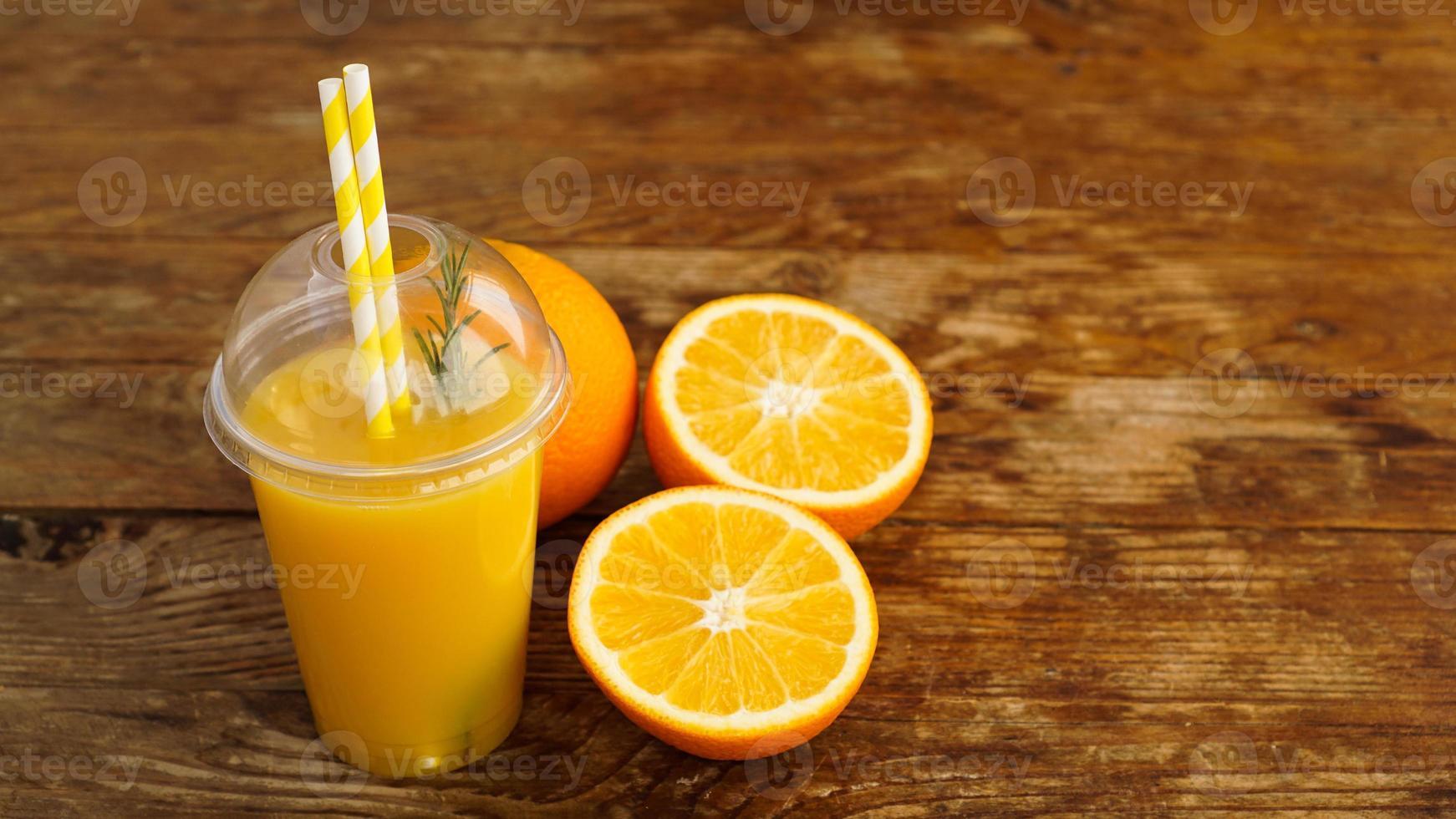 sinaasappelsap in fastfood gesloten beker met buizen op houten tafel foto