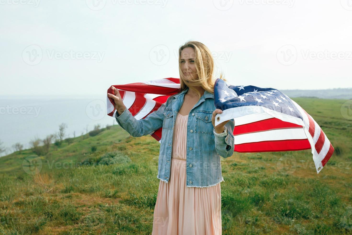 een meisje in een koraaljurk en een spijkerjasje houdt de vlag van de VS vast foto