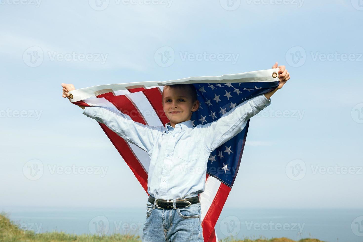 een kleine jongen houdt een vlag van de verenigde staten tegen de lucht foto