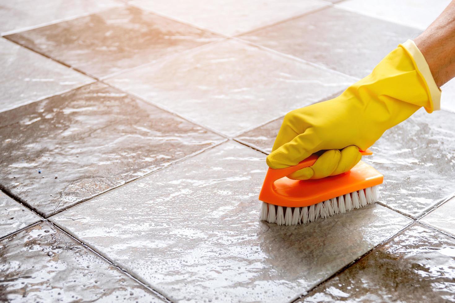 met behulp van een plastic vloer scrubber om de tegelvloer te schrobben. foto