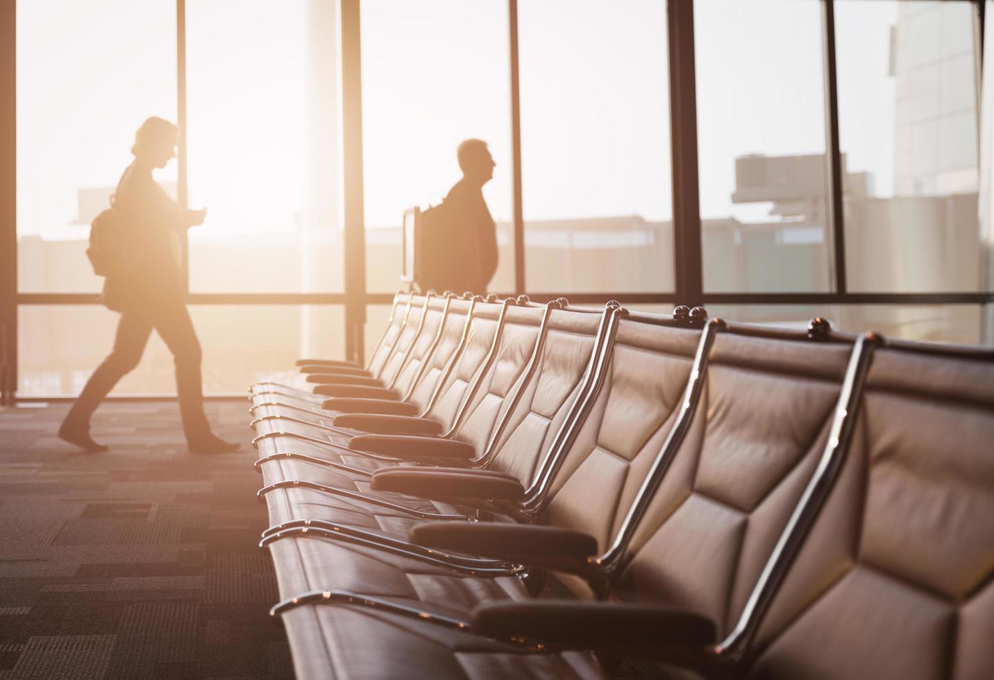 lege stoel met lopende passagiers naar hun vlucht foto