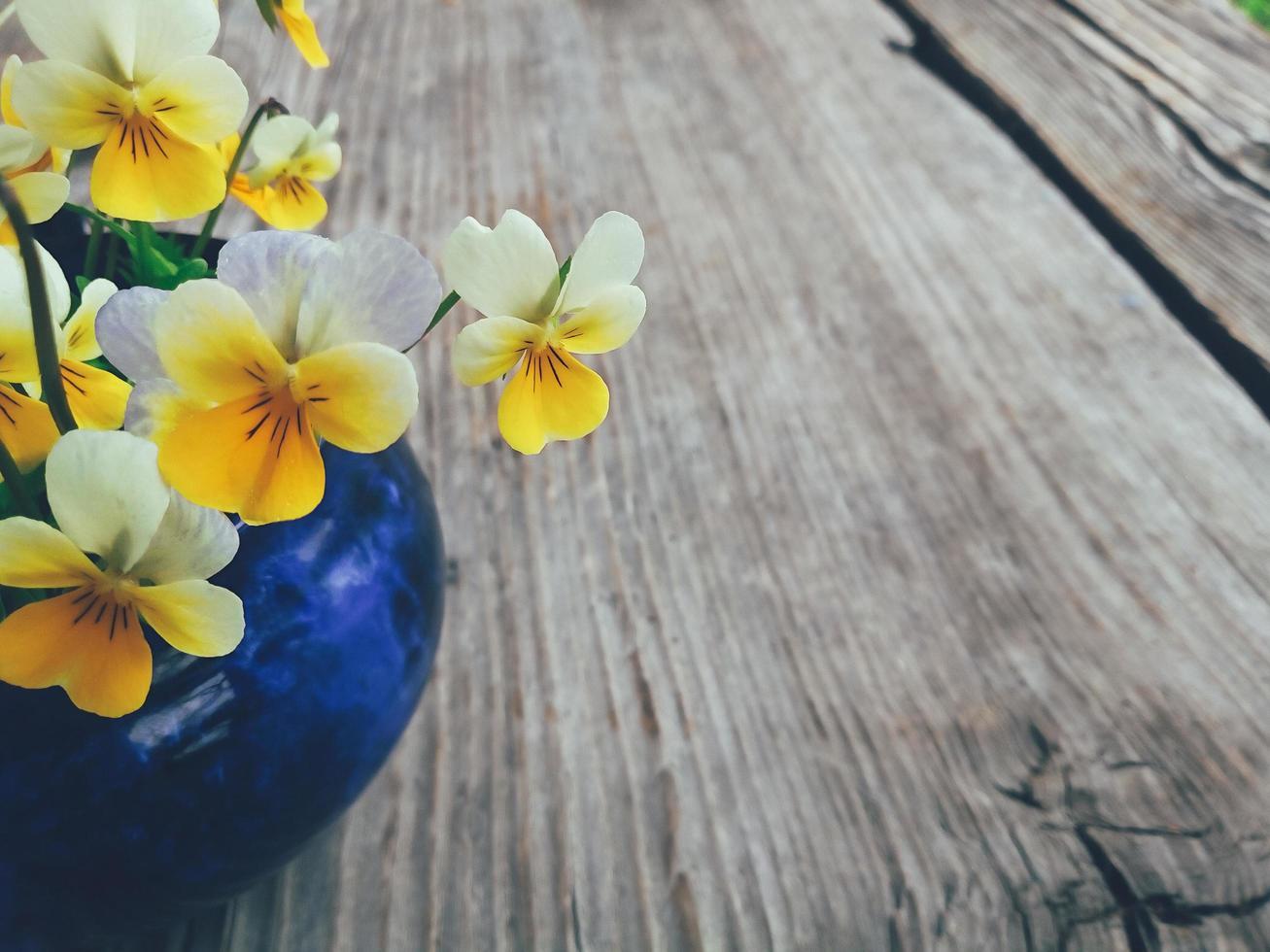 gele kus-me-snelle bloemen in blauwe keramische beker, op houten veranda achtergrond. stilleven in rustieke stijl. close-up bekijken. zomer of lente in de tuin, platteland lifestyle concept. kopieer ruimte foto