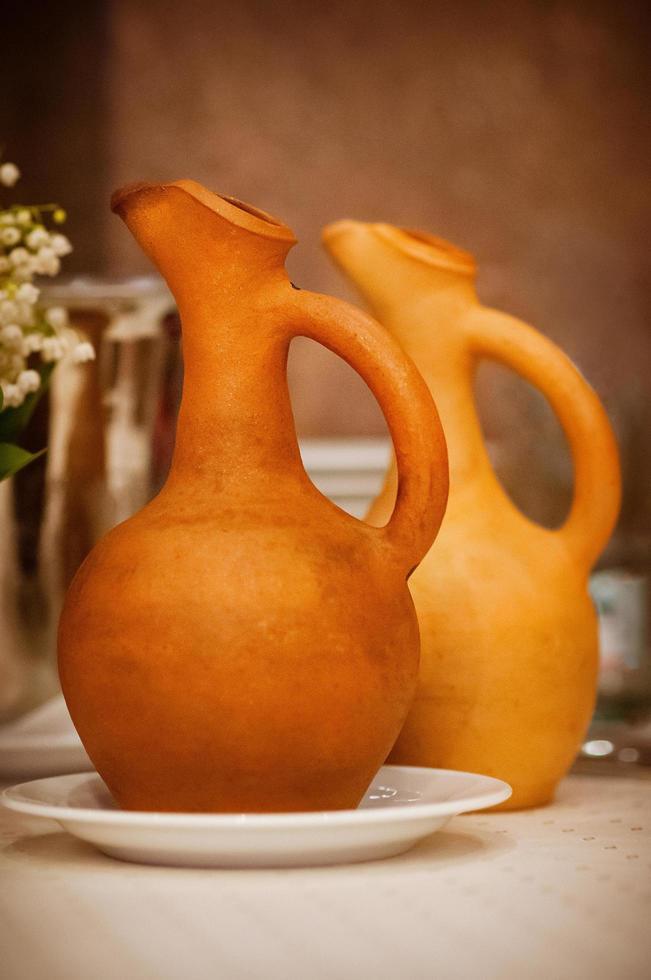 zacht gefocuste wijnkannen van terracotta kleur op tafel, familierestaurant, lunchtijd, eenvoudige stijl foto