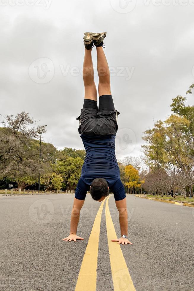 man die een handstand doet in het midden van de weg foto