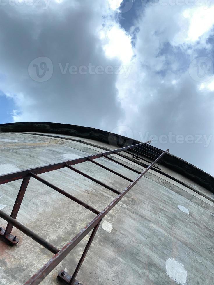 uitzicht op zoek naar een verroeste stalen ladder die omhoog gaat in een betonnen watertank foto