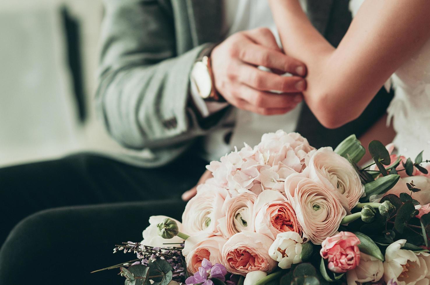 bruidsboeket met wazige bruid en bruidegom op de achtergrond foto