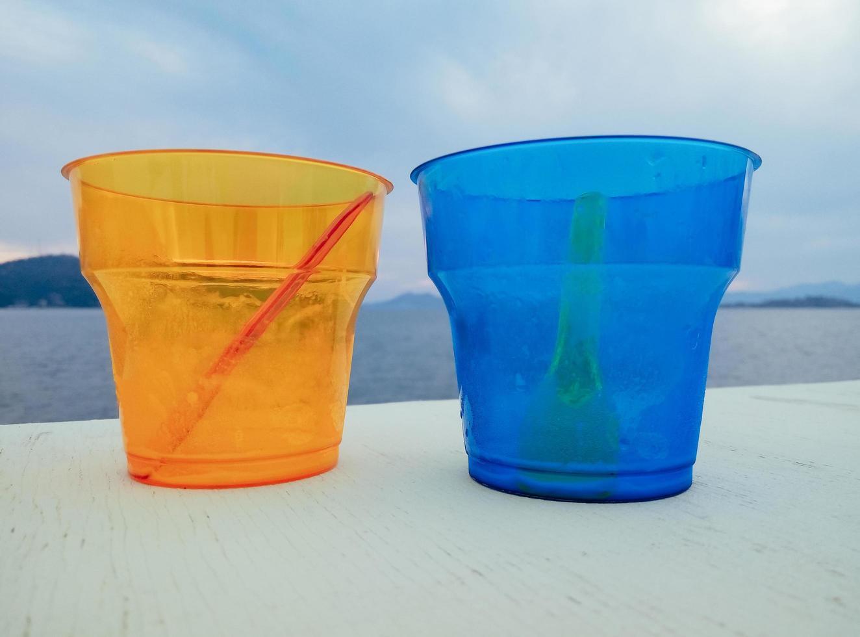 twee kleurrijke lege plastic bekers op het strand foto