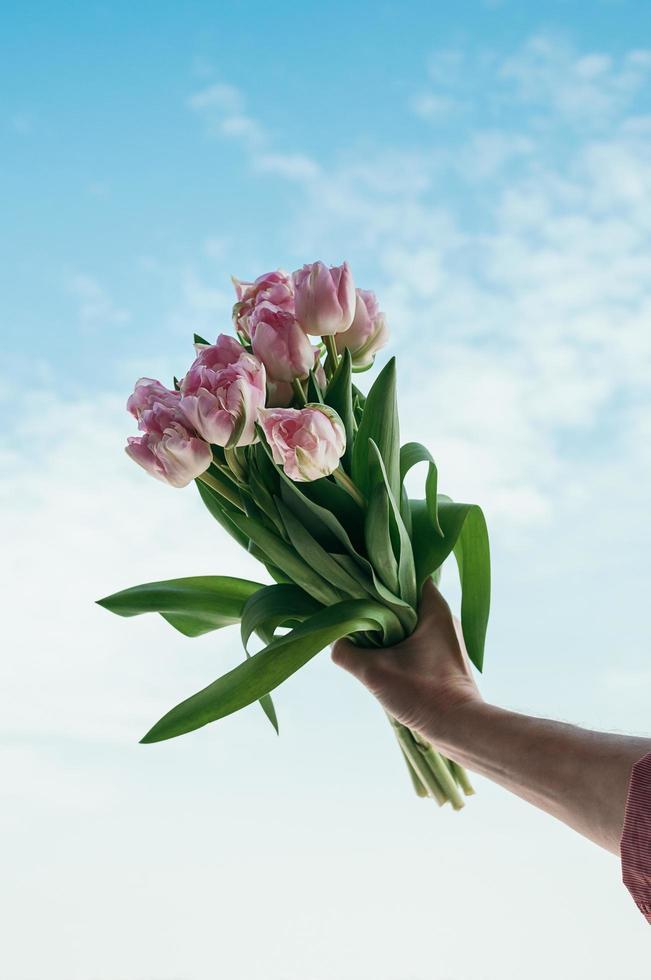 boeket van roze bloemen ter beschikking tegen blauwe hemelachtergrond foto