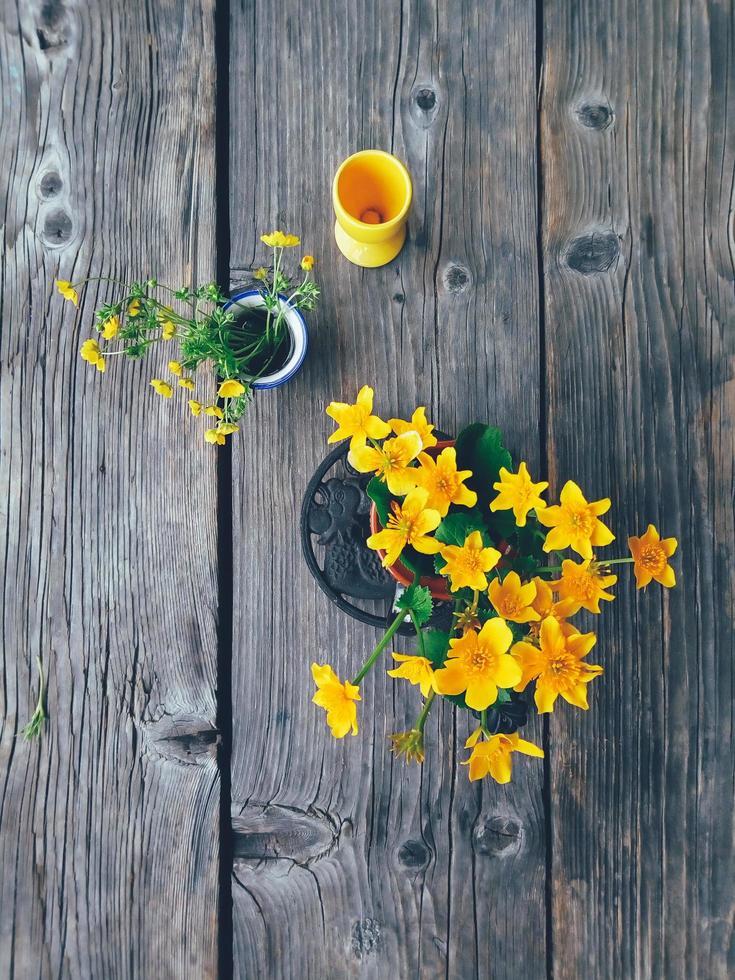 veld gele bloemen in kleurrijke vazen bovenaanzicht foto
