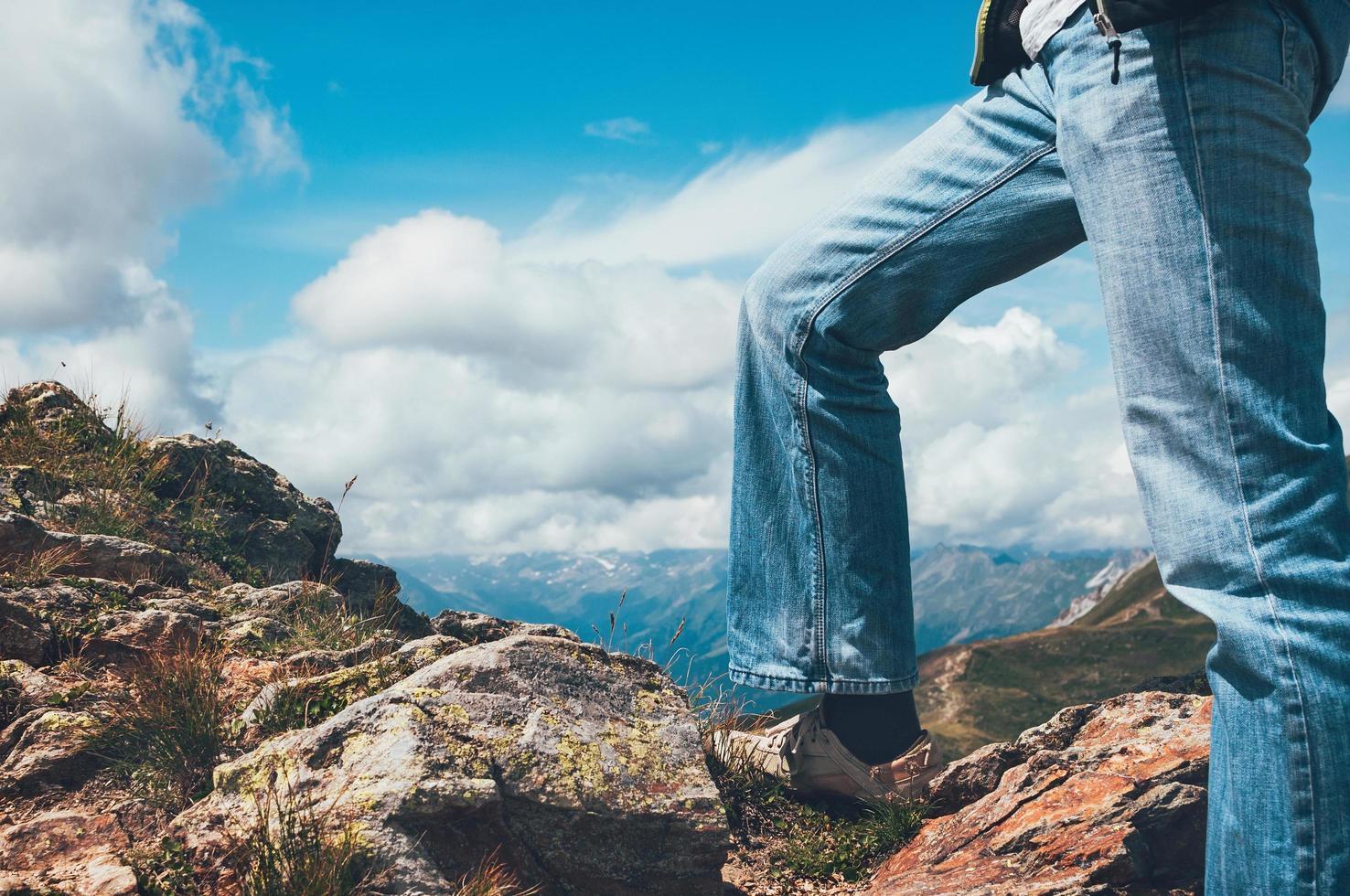 man benen staande op de top van de klif foto