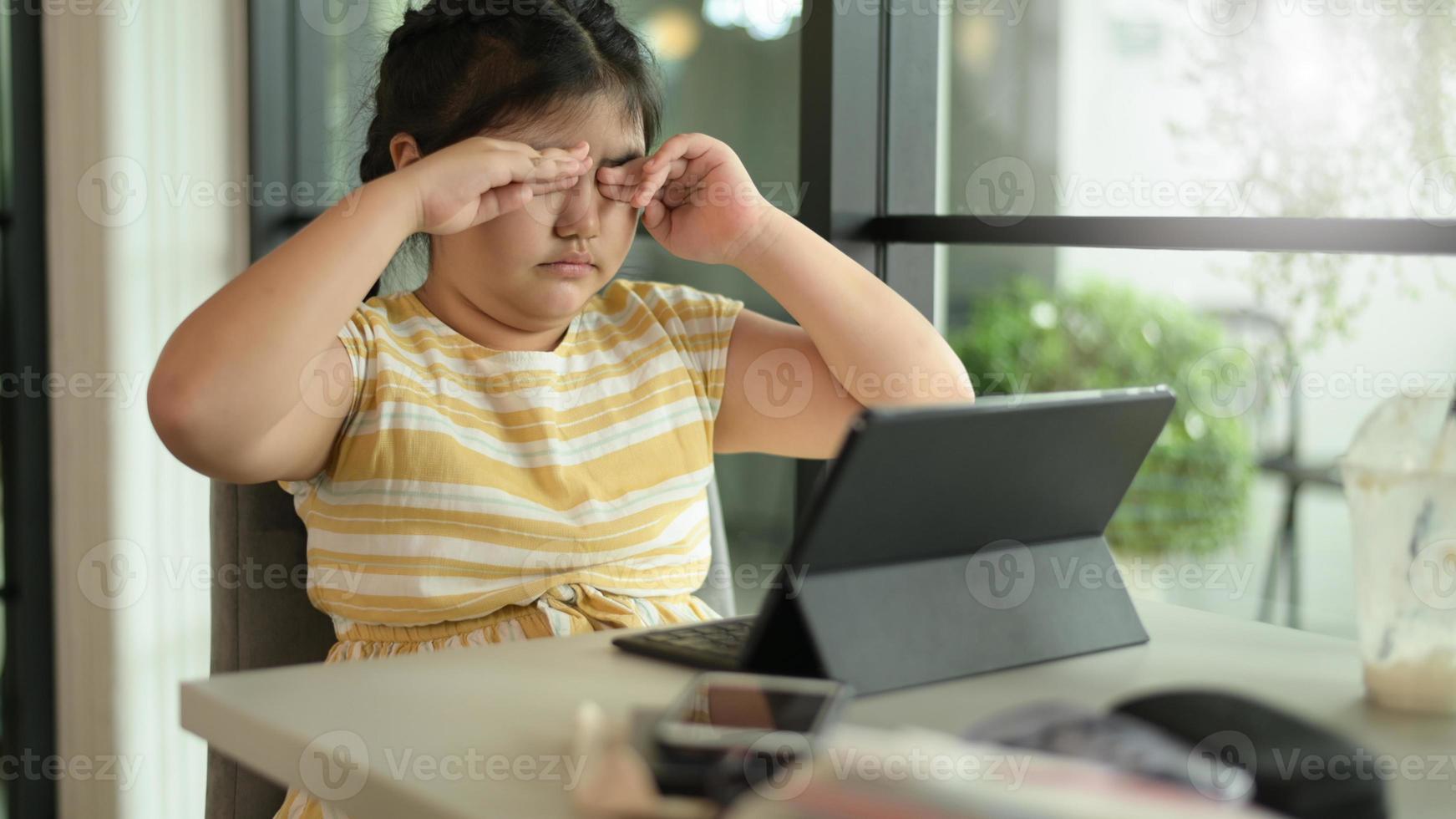 aziatisch kindmeisje sluit haar ogen om te rusten van het gebruik van een tablet. foto