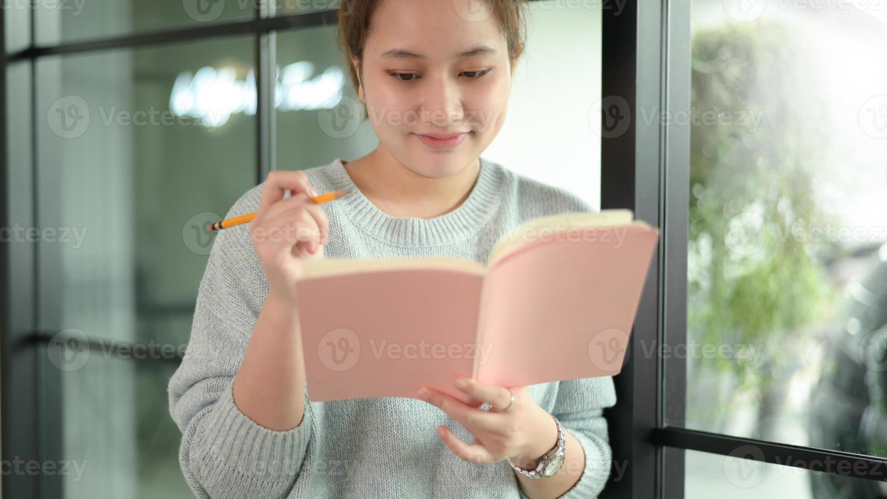 een tiener Aziatische vrouw met een pen staat bij het raam. foto