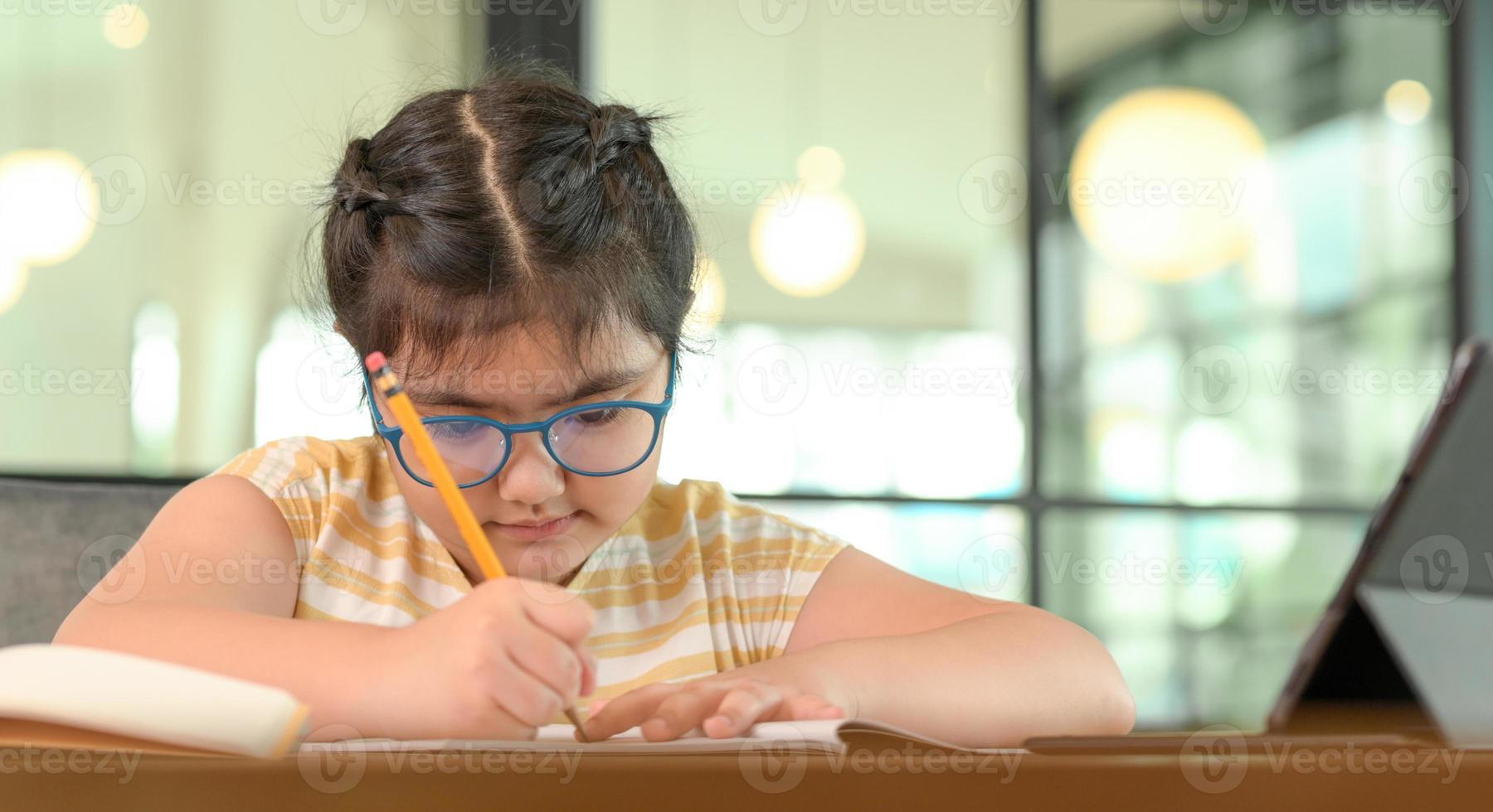 kind meisje met bril studeert thuis met serieuze uitdrukking. foto