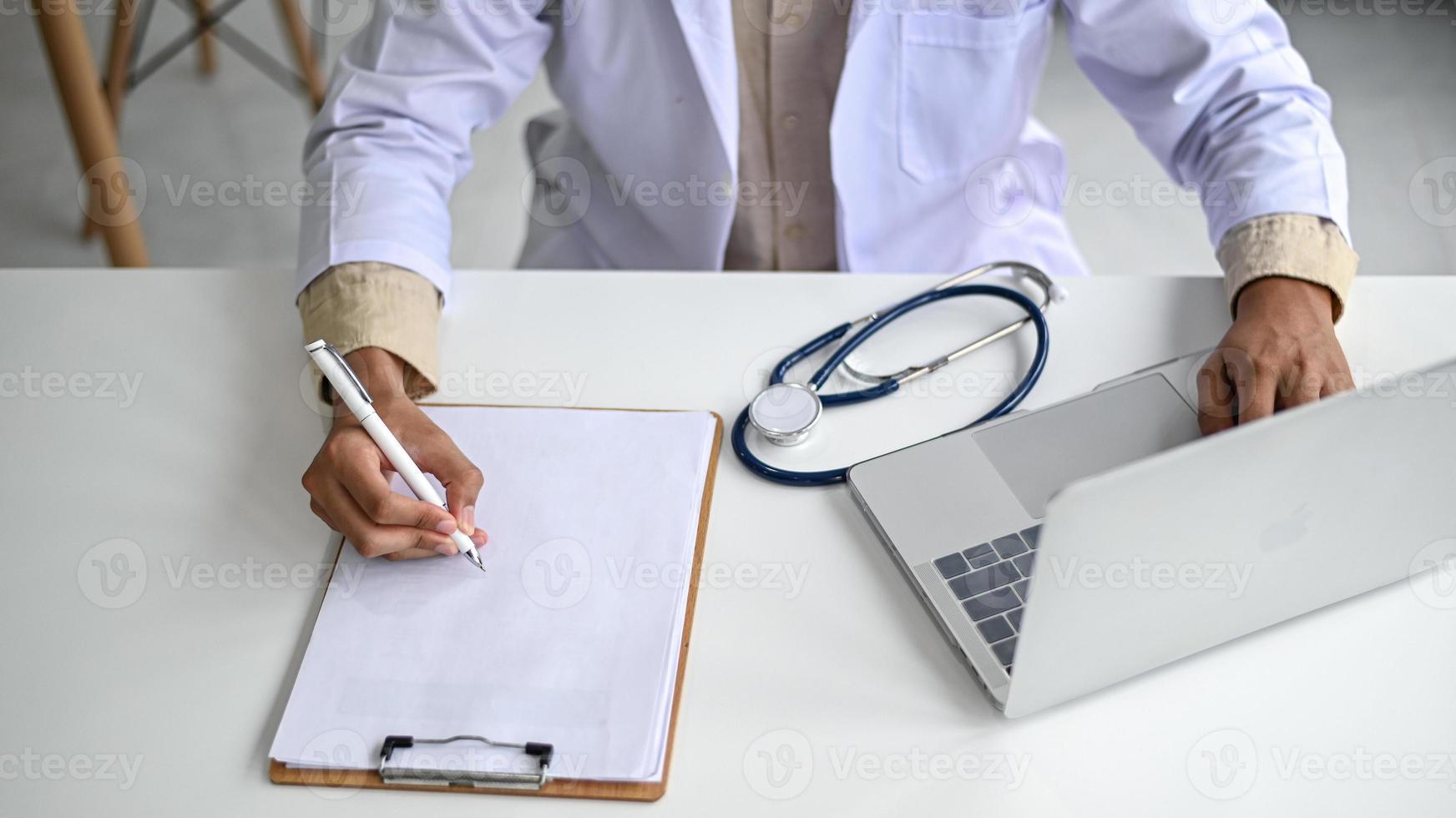 een medische professional in een laboratoriumjas houdt een potlood op een leeg dossier. foto