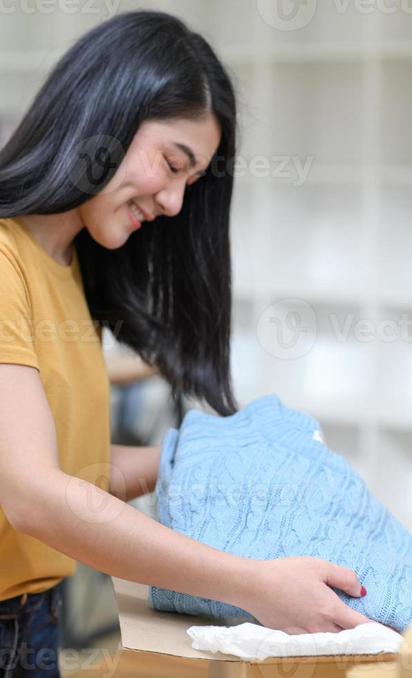 vrouw die truien in dozen verpakt voor verzending, online verkoopt. foto
