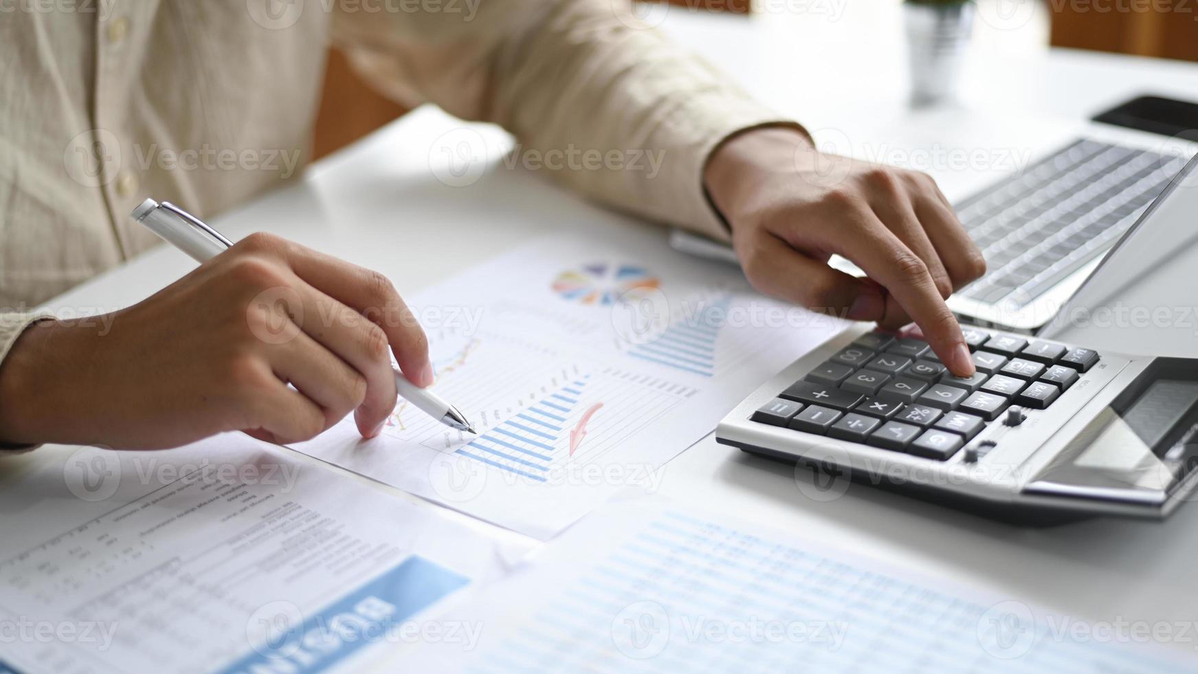 close-up shot van hand wijzende pen naar grafiekgegevens en het gebruik van rekenmachine. foto