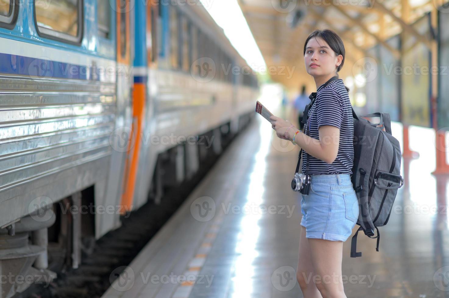 vrouwelijke internationale reiziger met kaart met rugzak die op de trein wacht. foto