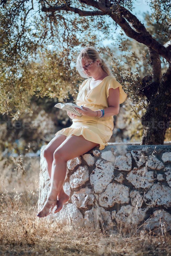een blonde vrouw op blote voeten in een gele zomerjurk foto